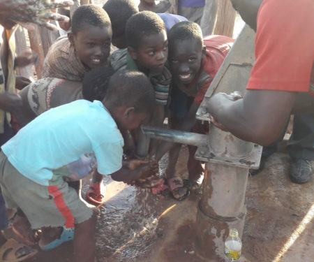 Muuka village children eagerly reach for clean water now flowing from a fixed water pump.