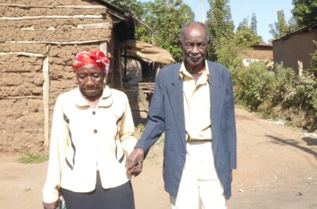Kenyan couple holds hands as they walk to the car that will take them for sight-saving surgery