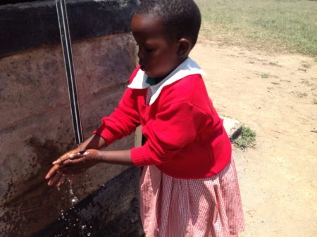 African child washing her hands to prevent the spread of trachoma.