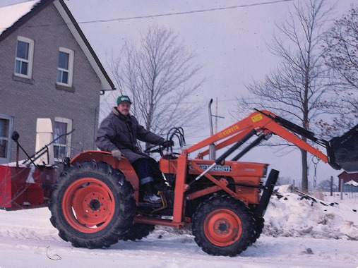 Roland with his tractor. He used it to rescue stuck cars during snowstorms, in exchange for donations to Operation Eyesight.