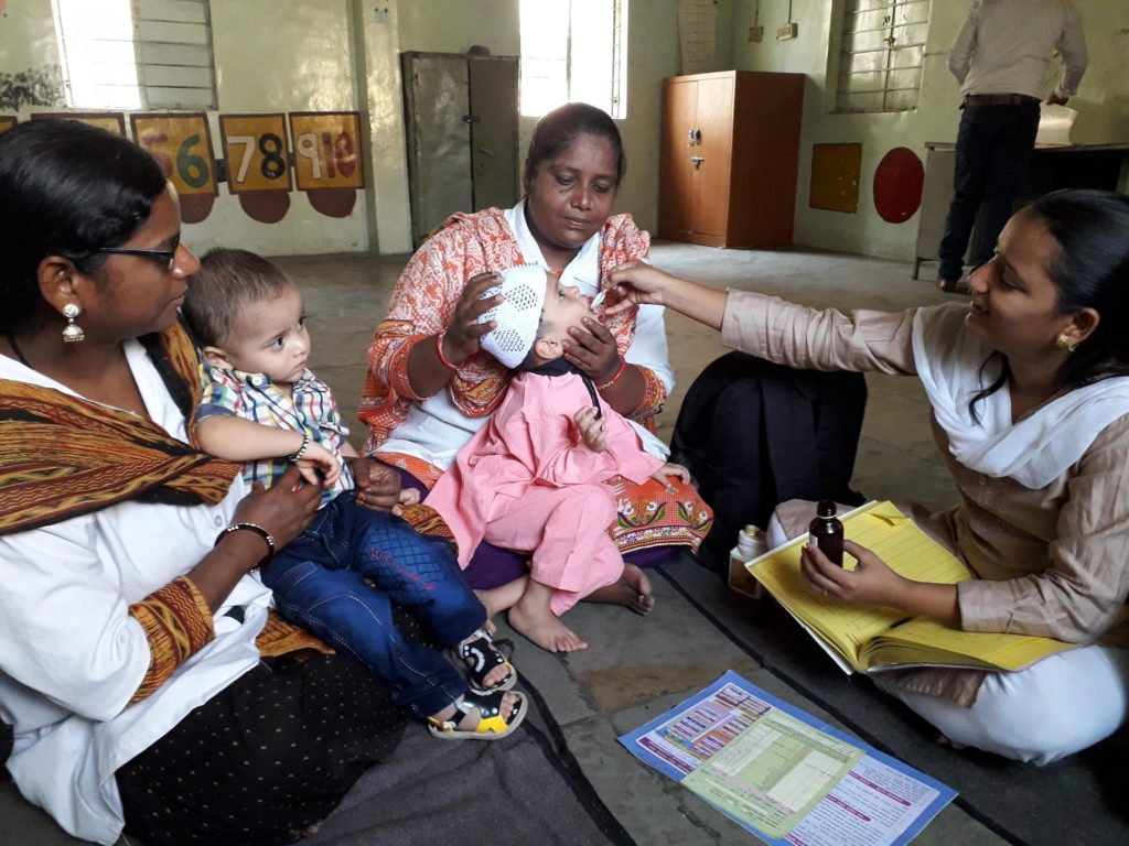 nurses administer vitamin A supplements to child in India
