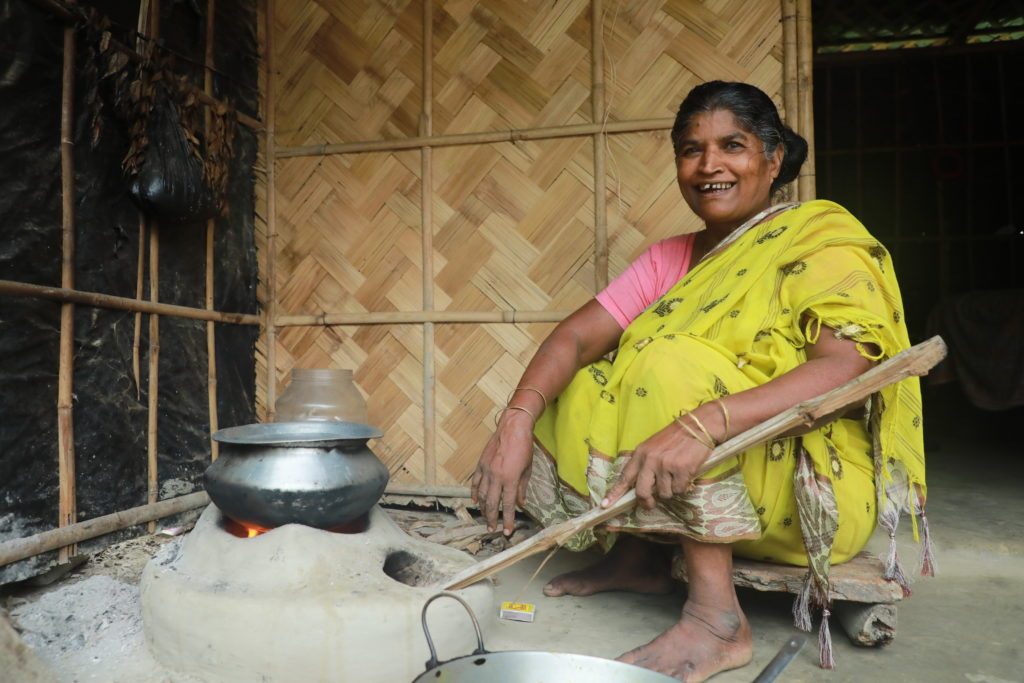 Savitri in her kitchen sitting by a stove made of mud.