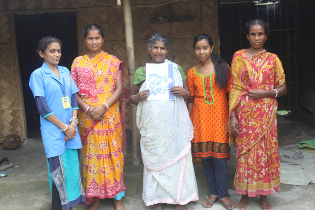Sabitri stands with her family members and a community health worker in front of her home.