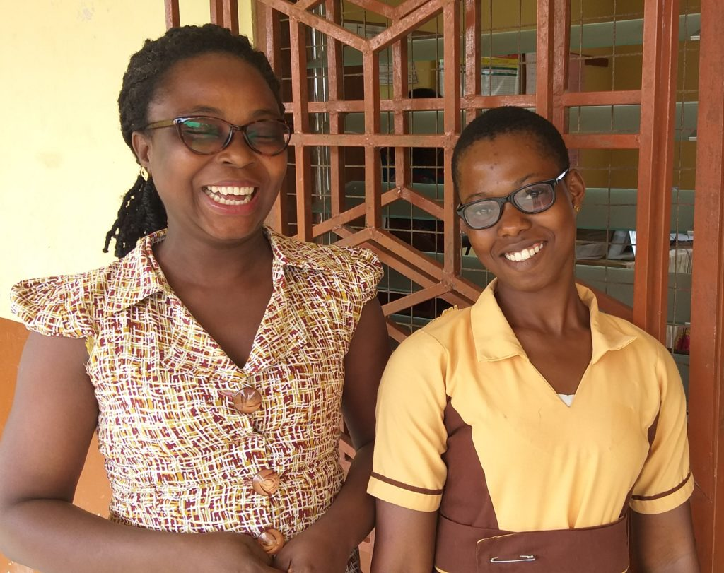Jennifer stands with her teacher, smiling at the camera
