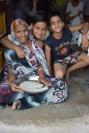 Premabai sits with her grandson as she sorts through a plate of rice grains