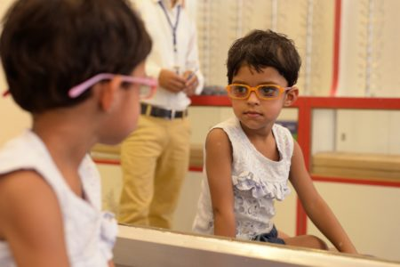 Child, wearing eyeglasses, looking at her reflection in a mirror