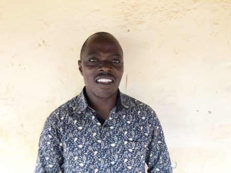 Kizito standing in front of a wall, looking at the camera