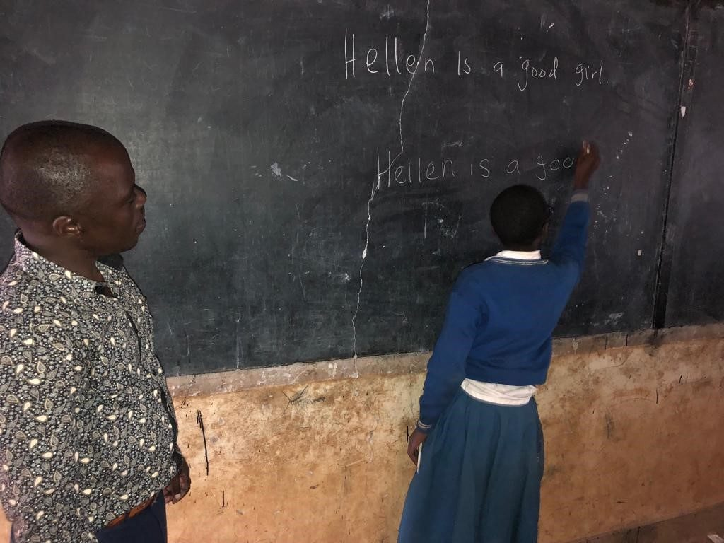 Kizito observes one of his students writing on the black board